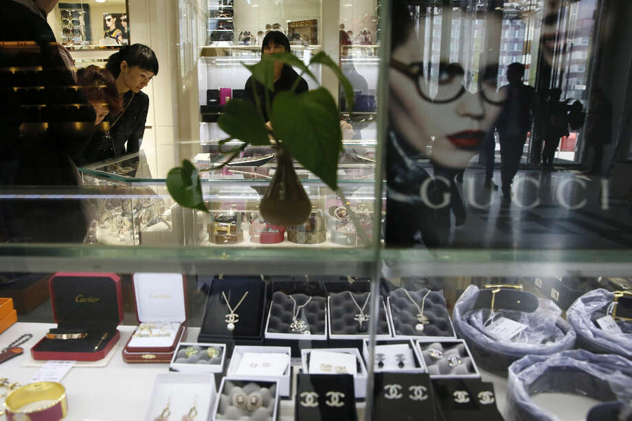 In this Wednesday, April 8, 2015 photo, customers look at products in a shop selling refurbished or second-hand items from brands such as Gucci, Chanel and Cartier at the Silk Street market in Beijing. Gucci has won at least three cases against counterfeiters in Chinese courts since 2008, but was awarded a combined total of only 650,000 yuan ($104,560) in damages. (AP Photo/Ng Han Guan)
