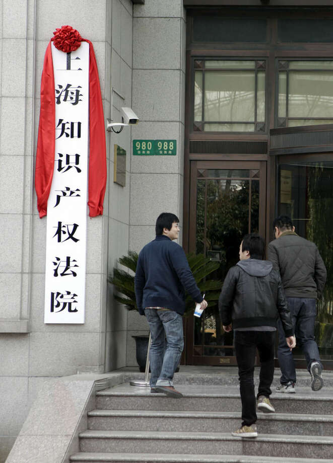 """In this March 24, 2015 photo, people walk up stairs next to a sign reading """"Shanghai Intellectual Property Court"""" in Shanghai. As China seeks growth from innovation, intellectual property protection has become more important to its top leadership. China opened three intellectual property courts late last year, symbols of a growing commitment to fight counterfeiting that has been felt as far away as Washington. (AP Photo/Paul Traynor)"""