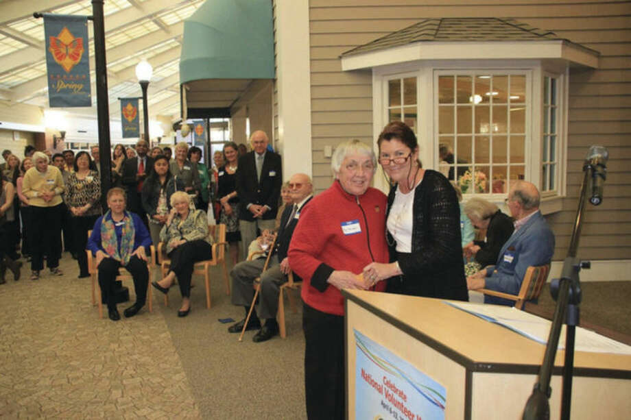 Contributed photoLong-time Waveny volunteer Fiz Tomaselli, wearing a name tag, is presented with an award by Debbie Perron, director of volunteers for Waveny, for her 3,700 volunteer hours of service.