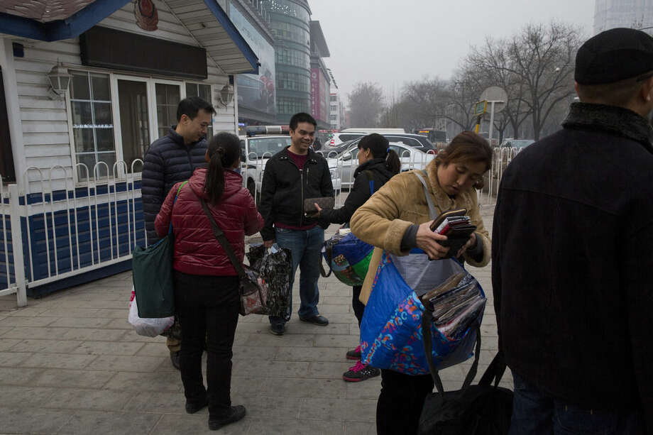 In this Monday, March 16, 2015 photo, street vendors offer counterfeited products to tourists outside a police post in front of the Silk Street market in Beijing. China's top leadership has begun to take intellectual property protection seriously as it steers the economy away from low-end manufacturing toward innovation, but many critics say its courts are not yet up to the task. (AP Photo/Ng Han Guan)