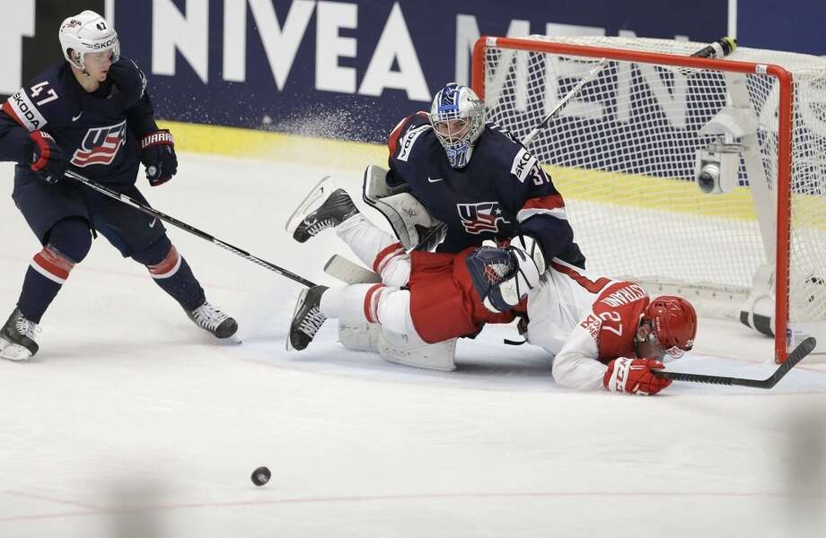 Denmark's Oliver Bjorkstrand collides with Connor Hellebuyck of the USA and Torey Krug of the USA, left, during the Hockey World Championships Group B match in Ostrava, Czech Republic, Friday, May 8, 2015. (AP Photo/Sergei Grits)