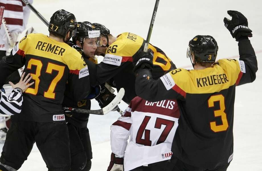 Germany's Michael Wolf, 2nd left, celebrates with teammates Patrick Reimer, left, Daniel Pietta, 2nd right and Justin Krueger, right, during the Hockey World Championships Group A match in Prague, Czech Republic, Friday, May 8, 2015. (AP Photo/Petr David Josek)