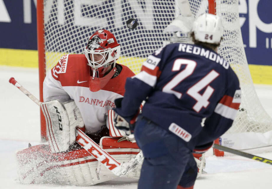 The puck shot by Zach Redmond of USA, right, goes wide after hitting Denmark's Sebastian Dahm, left, during the Hockey World Championships Group B match in Ostrava, Czech Republic, Friday, May 8, 2015. (AP Photo/Sergei Grits)