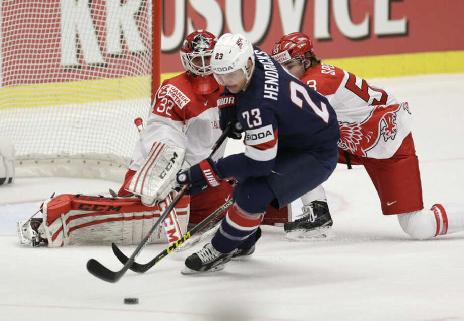 Matt Hendricks of USA, center, tries to control a puck in front of Denmark's Thomas Spelling, right, and goalkeeper Sebastian Dahm, left, during the Hockey World Championships Group B match in Ostrava, Czech Republic, Friday, May 8, 2015. (AP Photo/Sergei Grits)