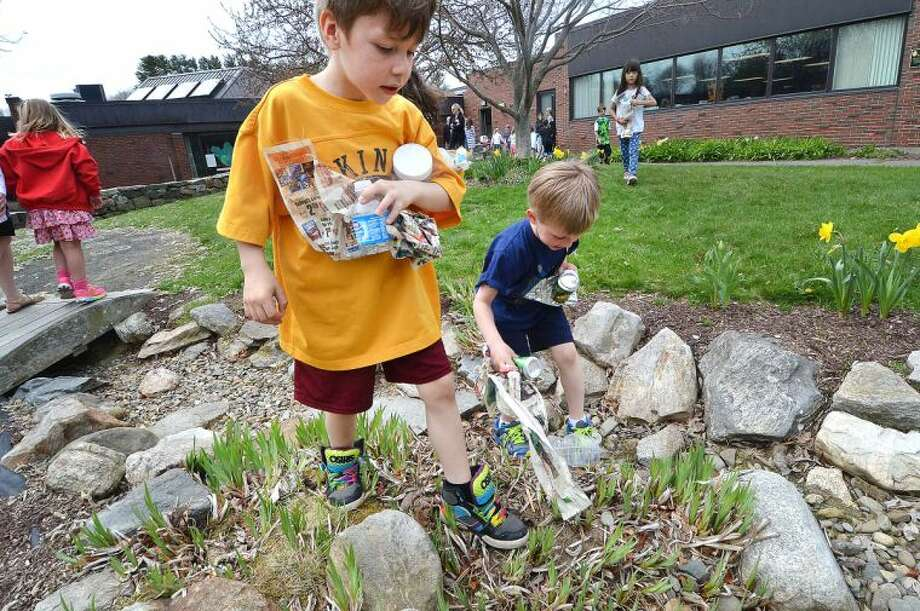 Hour Photo/Alex von Kleydorff 1st graders Loe Marin Gallo and Evan Lalor collect recyclables and place them in the proper containers to promote reclaim and reuse during Earth Day activities in the Outdoor Learning Center at Miller Driscoll School in Wilton Tuesday