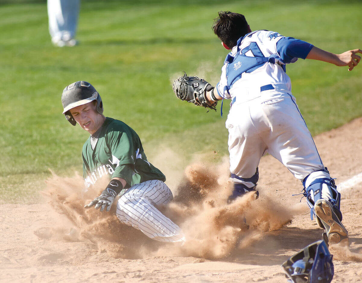 Hour photo/John Nash - Norwalk's Alex Barone slides safely across home plate with the game-winning run in the sixth inning of Fridays' FCIAC baseball game against Fairfield Ludlowe at Kiwanis Field in Fairfield.
