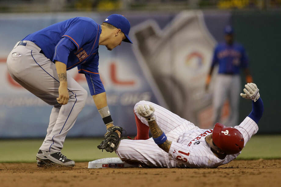 Philadelphia Phillies' Freddy Galvis, right, steals second base under the tag from New York Mets shortstop Wilmer Flores during the third inning of a baseball game, Friday, May 8, 2015, in Philadelphia. (AP Photo/Matt Slocum)