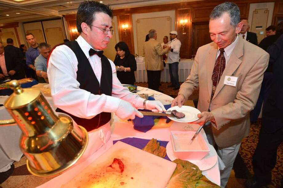 Hour Photo/Alex von Kleydorff Ceasar Ramirez trys the Filet Mignon at the buffet during the Silent Auction and Wine Tasting to benefit the PAL, Police Athletic League program at the Norwalk Police Department