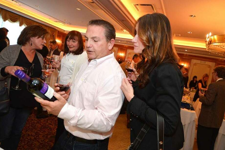Hour Photo/Alex von Kleydorff Tim Morrissette and fiance Sandra Newton sample a bottle of red wine supplied by BevMax for the wine tasting during the Silent Auction and Wine Tasting to benefit the PAL, Police Athletic League program at the Norwalk Police Department