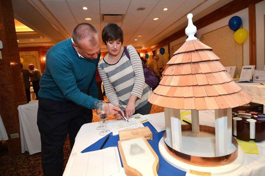 Hour Photo/Alex von Kleydorff Norwalk Police Chief Tom Kulhawik and his wife Julie bid on a handcrafted Bird feeder during a wine tasting and silent auction to benefit the Police Athletic League program