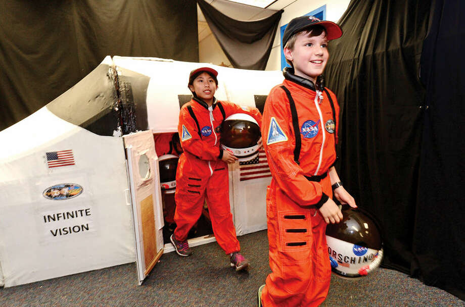 Hour photo / Erik Trautmann Mission Commander Darren Forschino leads the Young Astronauts out of the shuttle after the landing of the program's 20th mission, Infinite Vision, Friday at Columbus Magnet School.