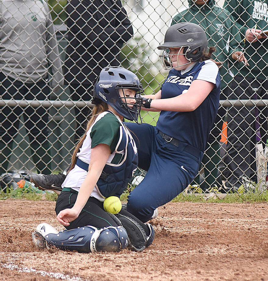 Staples baserunner Cat Connell, right, makes it to the plate safely as Norwalk catcher Sam Troetti can't come up with the throw on a delayed double steal in the third inning of Monday's FCIAC softball game at Ray Barry Field in Norwalk. The Wreckers won the game, 9-8.