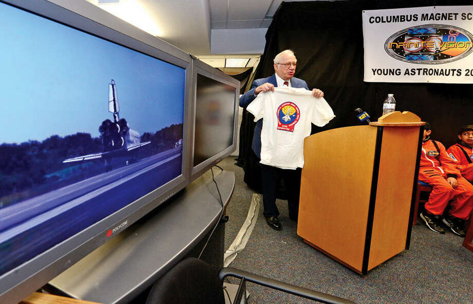 Hour photo / Erik Trautmann Program founder Art Perchino holds up a t-shirt from the first mission as the Young Astronauts program at Columbus Magnet School celebrates the landing of their latest mission, Infinite Vision, and the programs 20th anniversay Friday morning at the school.