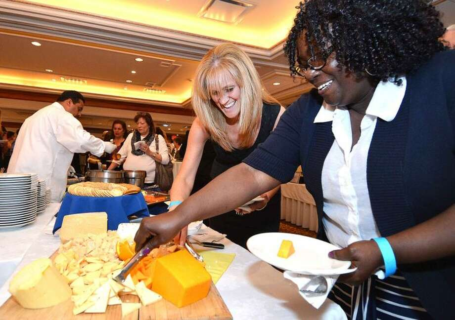 Hour Photo/Alex von Kleydorff Sheri Gradia and Juanita Sanford sample some cheeses at the buffet during the Silent Auction and Wine Tasting to benefit the PAL, Police Athletic League program at the Norwalk Police Department