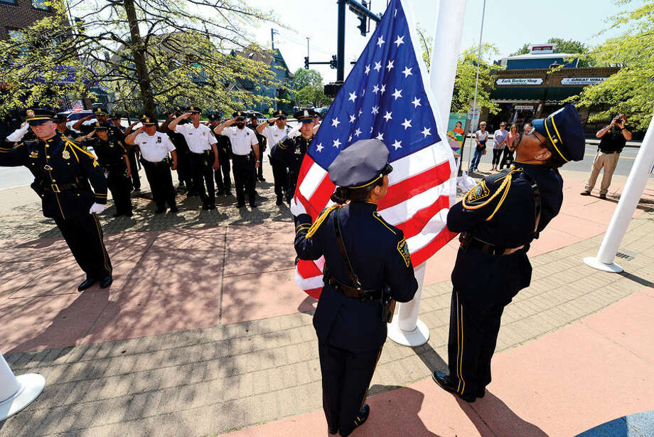 Hour photo / Erik Trautmann The Norwalk Police Honor Guard raise the colors during the annual Norwalk Police Department Police Memorial Service Friday at police headquarters.