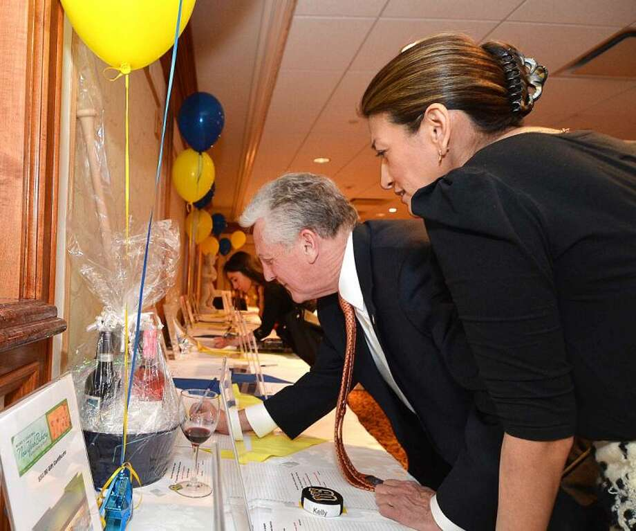 Hour Photo/Alex von Kleydorff Mayor Harry Rilling bids on a Tucci Baseball Bat with Lucia Cadena at the Silent Auction and Wine Tasting to benefit the PAL, Police Athletic League program at the Norwalk Police Department