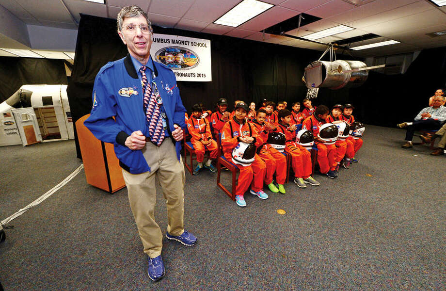 Hour photo / Erik Trautmann Commander and Chief and 6th grade teacher Andy Pearce congratulates the participants as the Young Astronauts program at Columbus Magnet School celebrates the landing of their latest mission, Infinite Vision, and the programs 20th anniversay Friday morning at the school.