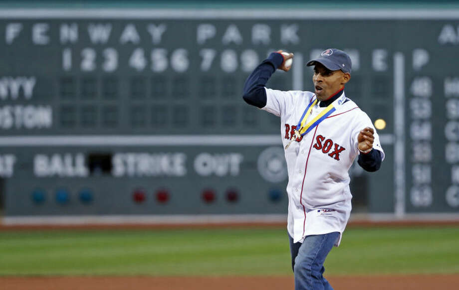 Meb Keflezighi, men's winner of the Boston Marathon earlier in the week, throws a ceremonial first pitch prior to a baseball game between the Boston Red Sox and the New York Yankees at Fenway Park in Boston, Wednesday, April 23, 2014. (AP Photo/Elise Amendola)