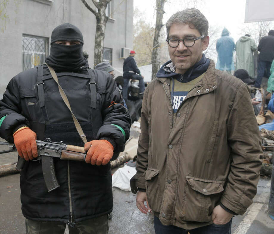 In this photo taken on Sunday, April 13, 2014, a reporter Simon Ostrovsky, right, stands next to a Pro-Russian gunman at a seized police station in the eastern Ukraine town of Slovyansk. Pro-Russian gunmen in eastern Ukraine say they are holding an American journalist captive. Ostrovsky, a journalist for Vice News, has not been seen since early Tuesday. (AP Photo/Efrem Lukatsky)