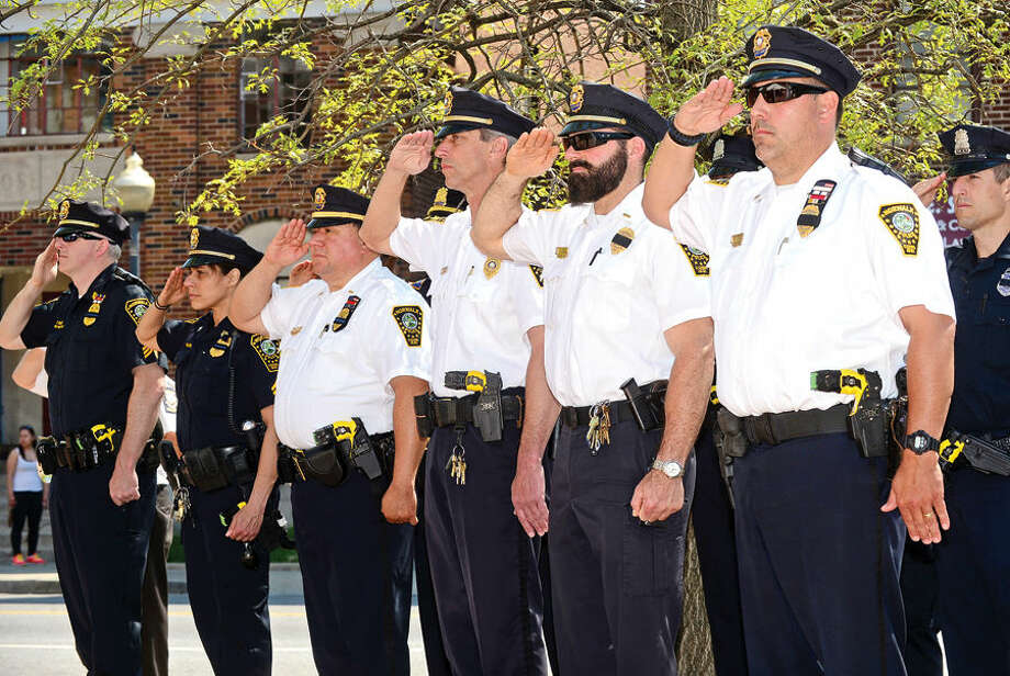 Hour photo / Erik Trautmann Norwalk police salute during the annual Norwalk Police Department Police Memorial Service Friday at police headquarters.