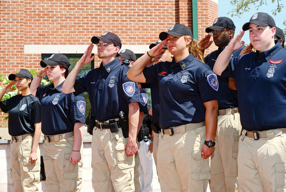 Hour photo / Erik Trautmann The Norwalk Police Exploerers salute during the annual Norwalk Police Department Police Memorial Service Friday at police headquarters.