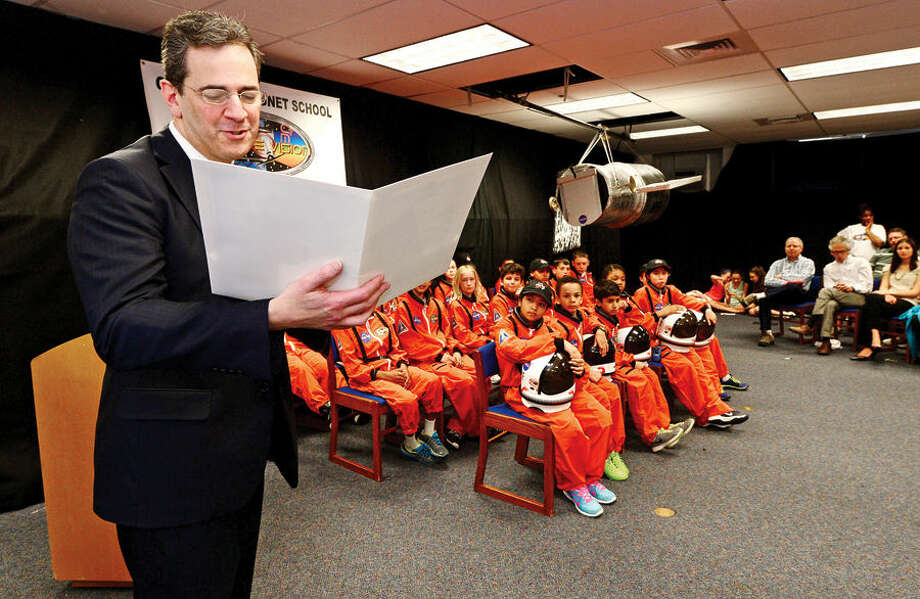 Hour photo / Erik Trautmann State Representative Chris Perone reads a letter of congratulations to the particpants as the Young Astronauts program at Columbus Magnet School celebrates the landing of their latest mission, Infinite Vision, and the programs 20th anniversay Friday morning at the school.