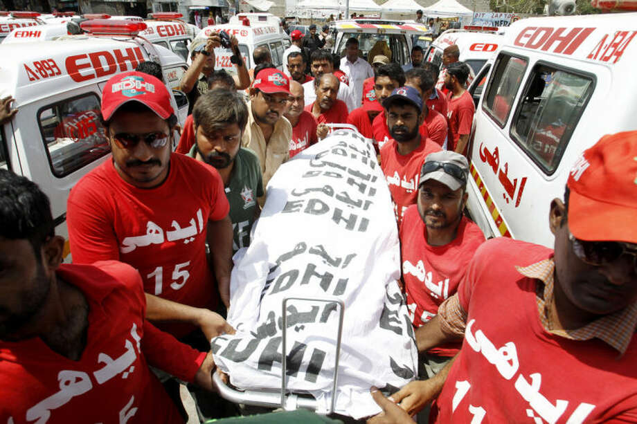 Pakistani volunteers carry a body of a bomb attack victim in Karachi Thursday, April 24, 2014. A Pakistani official says a bombing in the country's south targeted a police officer known for his anti-militant campaigns, killing him and his two friends. (AP Photo/Fareed Khan)