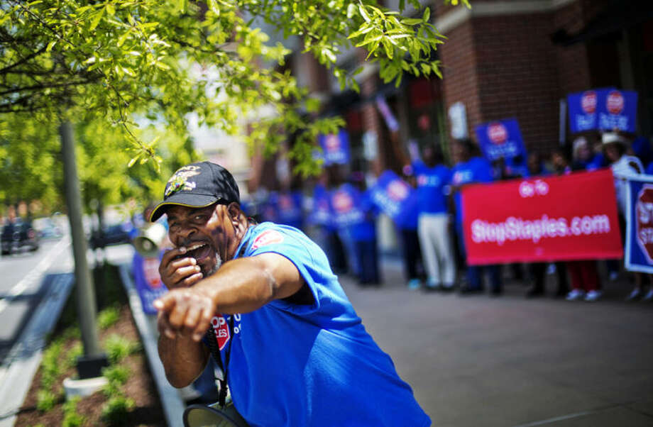 U.S. Postal employee LeRoy Lavender uses a bullhorn to chant to passing motorist during a protest outside a Staples store, Thursday, April 24, 2014, in Atlanta. Thousands of postal workers picketed outside Staples stores nationwide Thursday to protest a pilot program that allows the office supply chain to handle U.S. mail. (AP Photo/David Goldman)