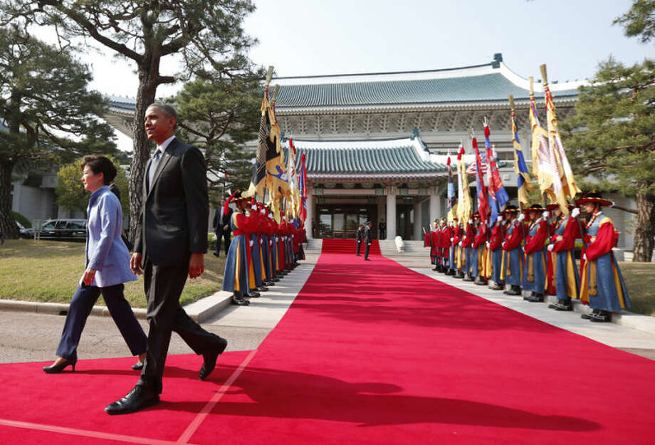 U.S. President Barack Obama is welcomed by South Korean President Park Geun-hye at the Blue House in Seoul, South Korea, Friday, April 25, 2014. Obama, continuing his four-nation Asia trip which began in Japan, is expected to underscore warnings against North Korean nuclear provocations, calls to lower tensions in regional territorial disputes, and words of condolence for the ferry disaster victims and the people of South Korea. (AP Photo/Charles Dharapak)