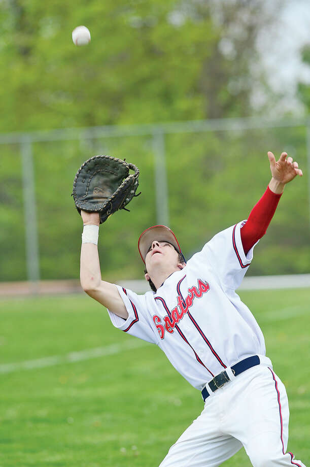 Hour photo / Erik Trautmann Brien McMahon High School's first baseman Mathew Galy catches a flyball in foul territory for the out during their baseball game against Fairfield Warde Saturday in Norwalk.