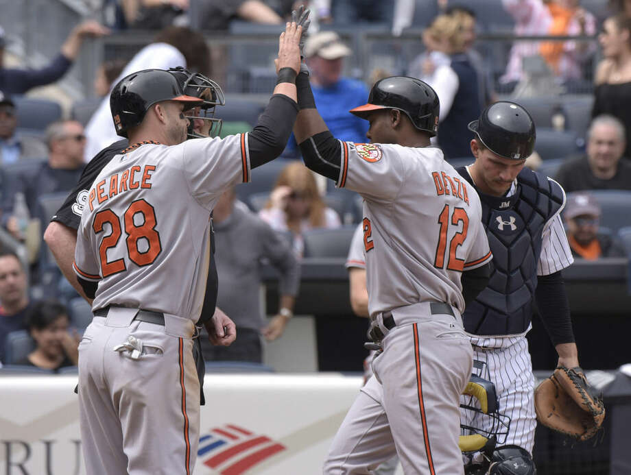 Baltimore Orioles' Alejandro De Aza celebrates with Steve Pearce, left, after De Aza hit a two-run home run as New York Yankees catcher John Ryan Murphy, right, reacts during the fourth inning of a baseball game against the New York Yankees Saturday, May 9, 2015, at Yankee Stadium in New York. (AP Photo/Bill Kostroun)