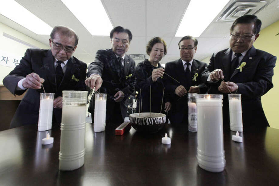 Mourners attend a temporary memorial for the victims of the sunken South Korean ferry Sewol at the Korean-American association center in Chicago, Thursday, April 24, 2014. The Sewol sank last week on a routine trip from the port of Incheon, near Seoul, to the southern island of Jeju. Of the 476 passengers and crew on board, 339 were children and teachers on a high school outing. (AP Photo/Nam Y. Huh)