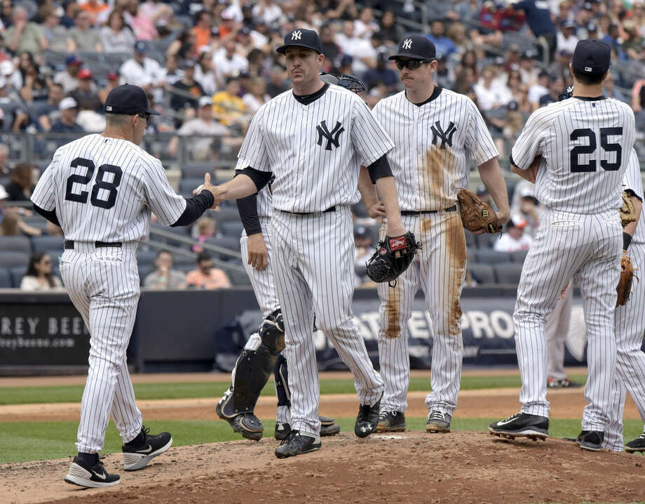 New York Yankees pitcher Chase Whitley hands the ball to manager Joe Girardi (28) as he leaves the game during the sixth inning of a baseball game against the Baltimore Orioles Saturday, May 9, 2015, at Yankee Stadium in New York. Yankees Chase Headley and Mark Teixeira (25) look on.(AP Photo/Bill Kostroun)