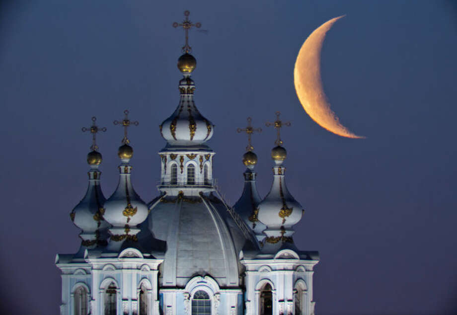 The moon rises in the sky above the domes of the Smolny Cathedral in St.Petersburg, Russia, Friday, April 25, 2014. One of St. Petersburg landmarks, the Smolny convent's main church was built between 1748 and 1764 by Italian architect Francesco Bartolomeo Rastrelli. (AP Photo/Dmitry Lovetsky)