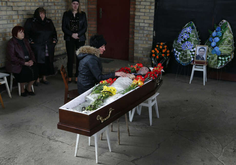 The body of Ukrainian councilman Volodymyr Rybak, lies in the coffin prior to his funeral after his body was found on Tuesday after his alleged abduction by pro-Russian insurgents in the eastern city of Horlivka, Ukraine, Thursday, April 24, 2014. (AP Photo/Sergei Grits)
