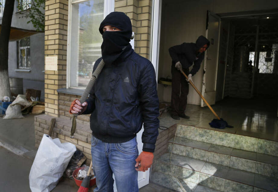 A pro Russian masked militant guards a seized police station in Slovyansk , eastern Ukraine, Friday, April 25, 2014. Russian Foreign Minister Sergey Lavrov has accused the West of plotting to control Ukraine and said the pro-Russian insurgents in the southeast would lay down their arms only if the Ukrainian government clears out the Maidan protest camp in the capital Kiev. (AP Photo/Sergei Grits)