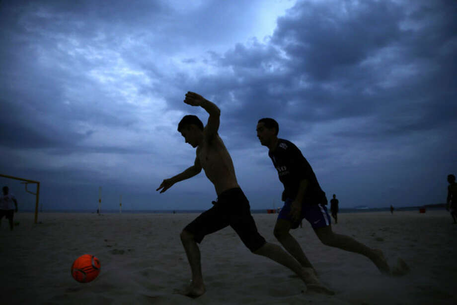 Brazilians and tourists play soccer on Copacabana beach, in Rio de Janeiro, Brazil, Wednesday, April 23, 2014. With the World Cup weeks away, Brazil has been struggling to get the country ready for the World Cup. Infrastructure work is far from completed and violent clashes continue to flare up in several cities. (AP Photo/Hassan Ammar)