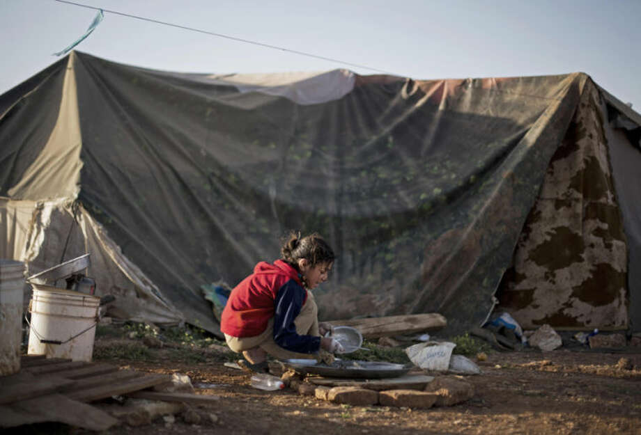 In this Tuesday, April 8, 2014 photo, a Syrian refugee girl washes dishes in front of her family tent in an unofficial refugee camp on the outskirts of Amman, Jordan. Some residents, frustrated with Zaatari, the region's largest camp for Syrian refugees, set up new, informal camps on open lands, to escape tensions and get closer to possible job opportunities.(AP Photo/Khalil Hamra)