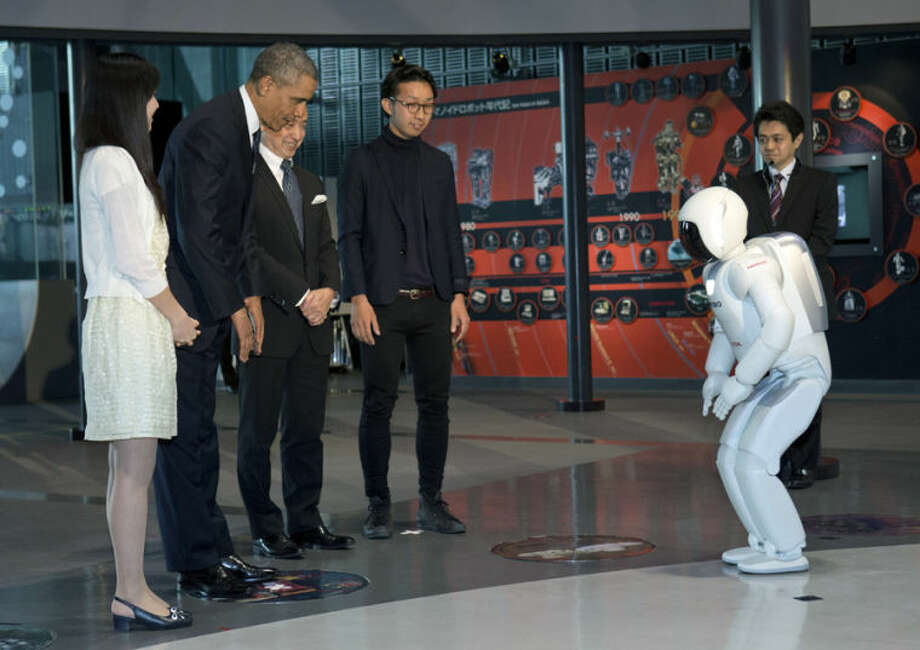 President Barack Obama and ASIMO, an acronym for Advanced Step in Innovative MObility, bow to each other during a youth science event at the National Museum of Emerging Science and Innovation, known as the Miraikan, in Tokyo, Thursday, April 24, 2014. Showing solidarity with Japan, Obama affirmed Thursday that the U.S. would be obligated to defend Tokyo in a confrontation with Beijing over a set of disputed islands, but urged all sides to resolve the long-running dispute peacefully. (AP Photo/Carolyn Kaster)