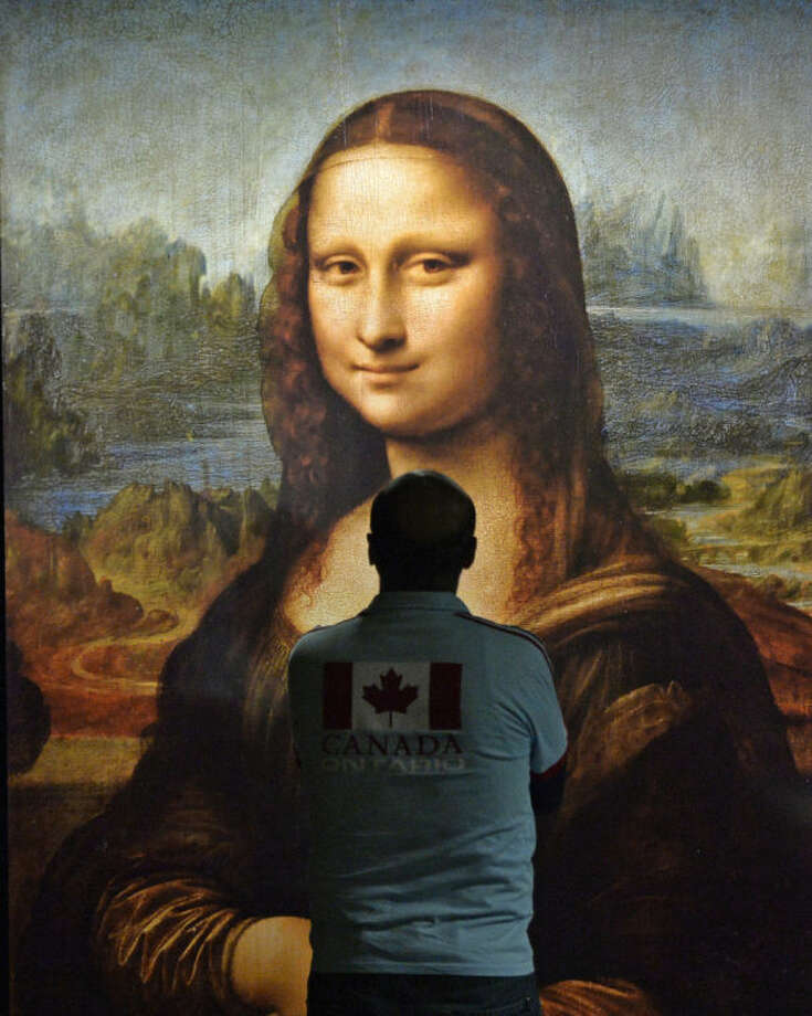 """A man watches a reprint of Leonardo da Vinci's Mona Lisa at the exhibition """"The appearance of beauty"""" in the Gasometer in Oberhausen, Germany, Thursday, April 24, 2014. (AP Photo/Martin Meissner)"""