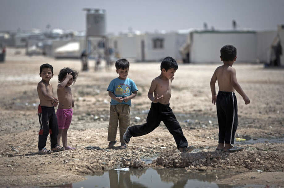 In this Thursday April 17, 2014 photo, Syrian children play under the heat of the midday sun at Zaatari refugee camp, near the Syrian border in Jordan. Life in this sprawling camp, Zaatari, is only getting harder for 130,000 residents, most of them fleeing fighting in south Syria. (AP Photo/Khalil Hamra)