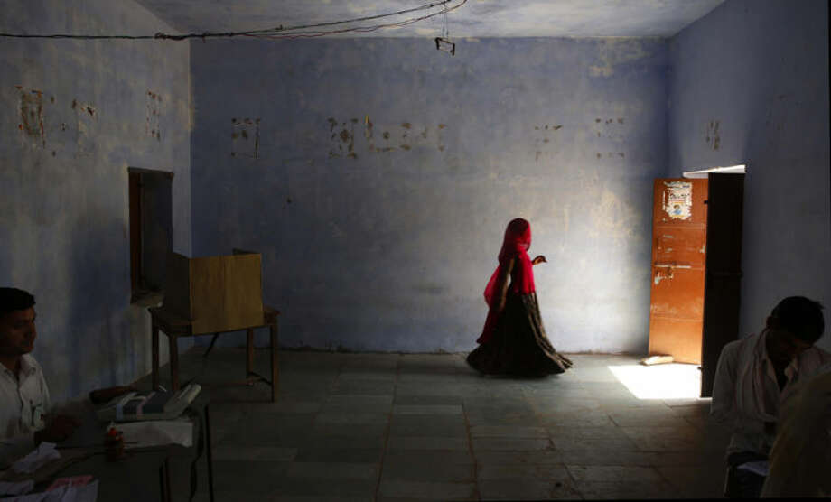 An Indian woman leaves after casting her vote in a village near Sawai Madhopur, in the Indian state of Rajasthan,Thursday, April 24, 2014. With 814 million eligible voters, India is voting in phases over six weeks. Results are expected May 16. (AP Photo /Manish Swarup)