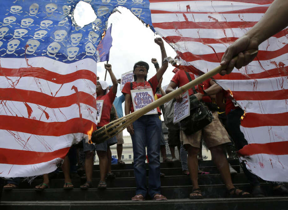 Protesters shout slogans as they burn a mock U.S. flag in an almost-daily protest against next week's visit of U.S. President Barack Obama Friday, April 25, 2014 in Manila, Philippines. Anti-US groups mounted their protests against Obama's visit as both Philippine and U.S. governments rush to finalize, for possible signing, the so-called Agreement on Enhanced Defense Cooperation (AEDC) which will allow larger US military presence in the country. (AP Photo/Bullit Marquez)