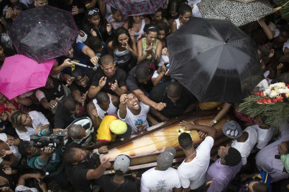 Relatives and friends of Douglas Rafael da Silva Pereira react around his coffin during his burial in Rio de Janeiro, Brazil, Thursday, April 24, 2014. A protest followed the burial of Douglas Pereira, whose shooting death sparked clashes Tuesday night between police and residents of the Pavao-Pavaozinho slum. (AP Photo/Felipe Dana)