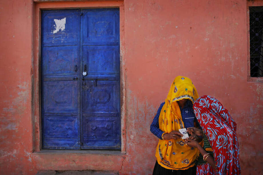 An Indian woman checks the voter identity card of another after casting votes during the sixth phase of polling of the Indian parliamentary elections at a village near Sawai Madhopur, Rajasthan state, India, Thursday, April 24, 2014. With 814 million eligible voters, India is voting in phases over six weeks. Results are expected May 16. (AP Photo /Manish Swarup)
