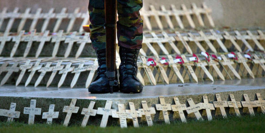 A soldier stands on a memorial filled with wooden crosses and red poppies during an Anzac Day service at Polygon Wood in Zonnebeke, Belgium on Friday, April 25, 2014. Anzac Day is commemorated by New Zealand and Australia to remember the service of those who fought in all wars. (AP Photo/Virginia Mayo)