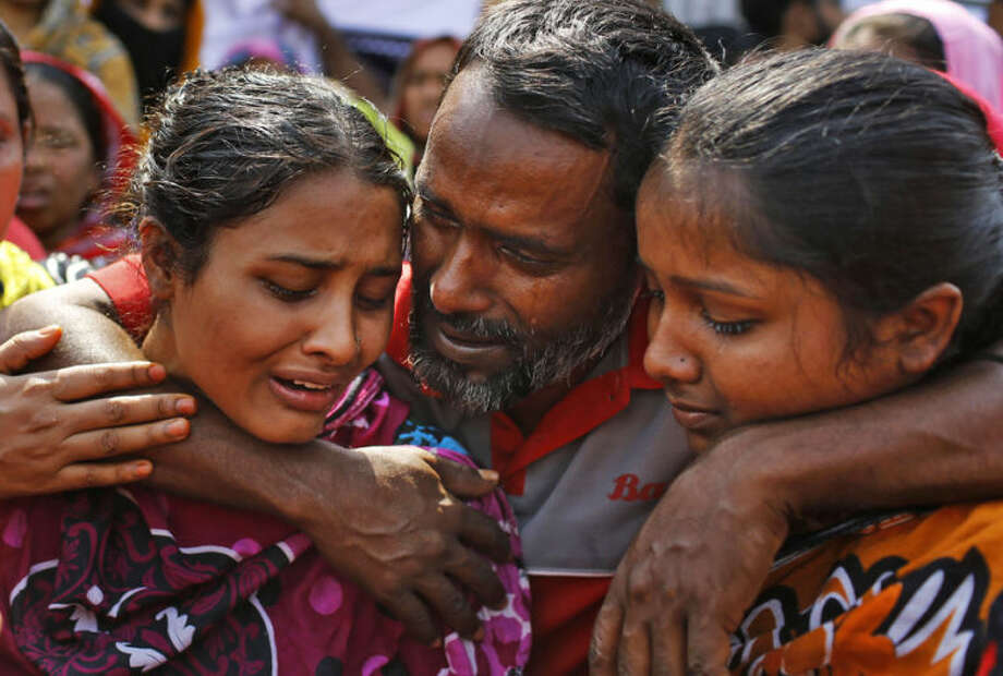 Relatives of victims mourn as they gather at the spot on the anniversary of last year's garment factory building collapse in Savar, near Dhaka, Bangladesh, Thursday, April 24, 2014. More than 1,100 people were killed when the illegally constructed, 8-storey building collapsed on April 24, 2013, in a heap along with thousands of workers in the five garment factories in the building. (AP Photo/A.M. Ahad)