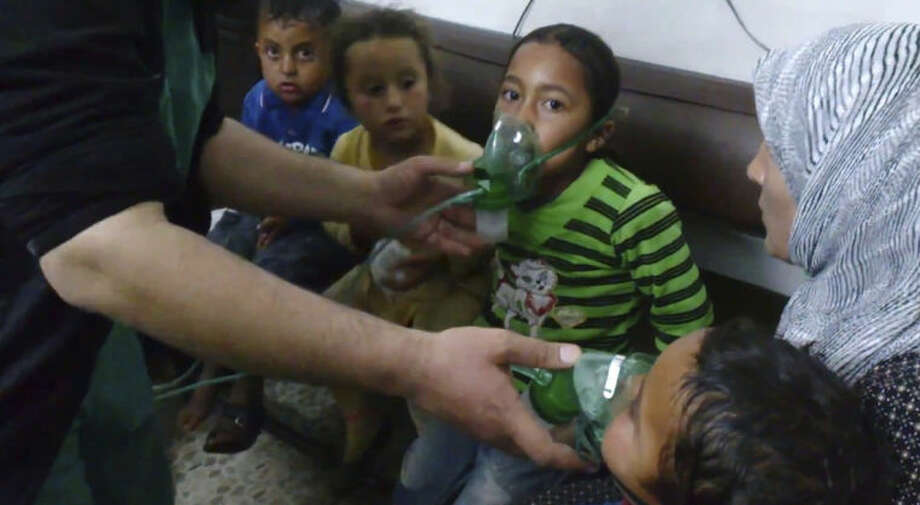 In this image taken from video obtained from the Shaam News Network, posted on April 16, 2014, an anti-Bashar Assad activist group, which has been authenticated based on its contents and other AP reporting, children are seen receiving oxygen in Kfar Zeita, a rebel-held village in Hama province some 200 kilometers (125 miles) north of Damascus. Syrian opposition activists and other witnesses tell The Associated Press that Syrian government forces have attacked rebel-held areas with poisonous chlorine gas in recent months. They say the attacks left scores of men, women and children coughing, choking and gasping for breath. The reports have been denied by the Syrian government and have yet to be confirmed by any foreign country or international organization. But if true, they highlight the limitations of the global effort to rid Syria of its chemical weapons. (AP Photo/Shaam News Network)