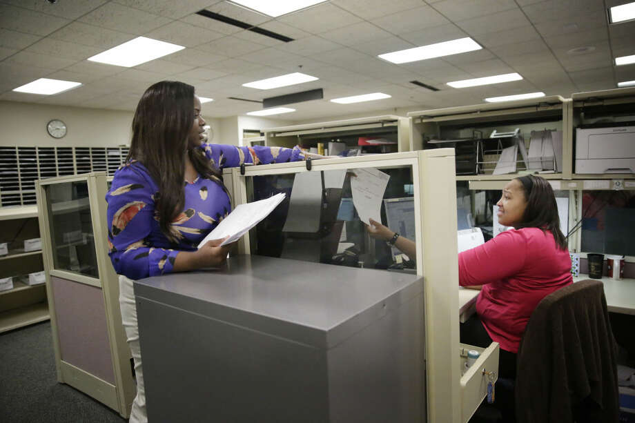 Trameka Daniels, left, hands Hillary Claibon, right, both of Montgomery, Ala., documents at the Alabama Circuit Court Clerk Criminal office, Thursday, May 7, 2015, in Montgomery, Ala. A trend is emerging among the states like Alabama showing large budget gaps. Shortfalls have been projected for the coming fiscal year in at least 22 states. (AP Photo/Brynn Anderson)