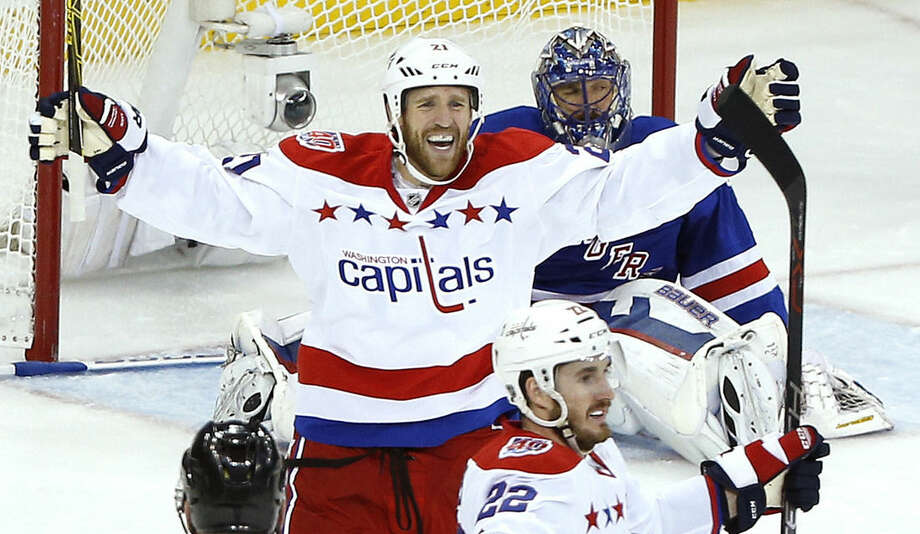 Washington Capitals center Brooks Laich (21) and left wing Curtis Glencross (22) celebrate a third period goal by Glencross against New York Rangers goalie Henrik Lundqvist during Game 5 in the second round of the NHL Stanley Cup hockey playoffs, Friday, May 8, 2015, in New York. (AP Photo/Julie Jacobson)